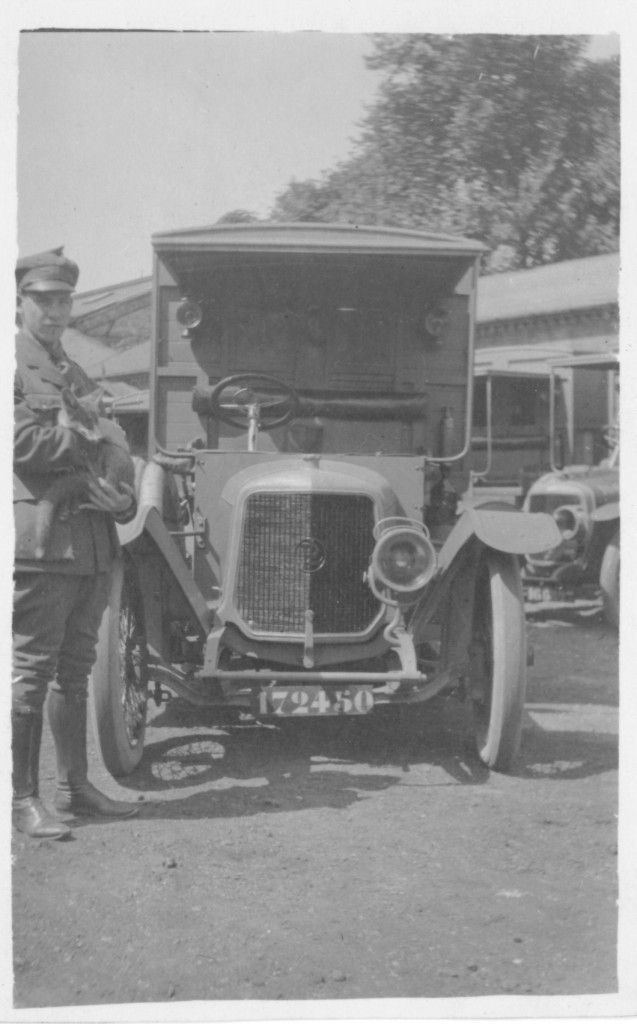 12. Ambulancier in dress uniform holding_Sammy_ a 2 month old Fox and mascot of Section O.C. My_Panhard_ Ambulance is in the background